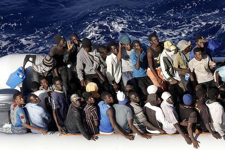 """Migranti di origine subsahariana a bordo di un gommone durante le operazioni di soccorso della nave """"Comandante Bettica"""" della Marina Militare nel Canale di Sicilia, 15 Settembre 2015. ANSA/ GIUSEPPE LAMI"""
